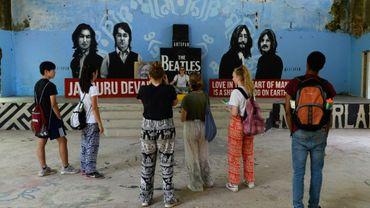 Des touristes devant une fresque murale représentant les Beatles dans l'ancien ashram du gourou Maharishi Mahesh Yogi partiellement rénové où le célèbre groupe a séjourné il y a 50 ans, le 18 juin 2018 à Rishikesh, dans le nord de l'Inde