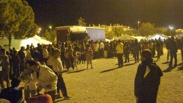 La foule fait la file pour recevoir à boire et à manger