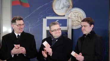 Le Premier ministre lituanien Algirdas Butkevicius (g), le président de la Banque de Lituanie Vitas Vasiliauskas (c), et le Premier ministre estonien Taavi Roivas (d) avec des euros symboliquement retirés le 1er janvier 2015 d'un distributeur de billets à Vilnius
