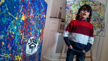 "7-year-old German artist Mikail Akar poses in front of a print edition of his ""Champi"" painting"