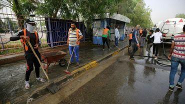 Des employés municipaux nettoient les lieux d'un attentat-suicide contre des cafés, dans le quartier majoritairement chiite d'al-Shoala, le 24 mai 2018 à Bagdad