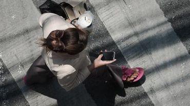 Une femme consulte son smartphone dans la rue