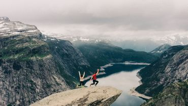 Two people jumping  on the Trolltunga