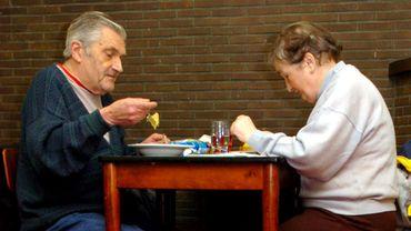 """Deux personnes profitent d'un repas chaud offert par """"Les petits riens"""" en décembre 2005."""