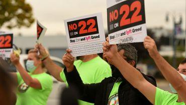 Des chauffeurs pour Uber et Lyft brandissent des panneaux contre la Proposition 22 à Oakland le 9 octobre 2020