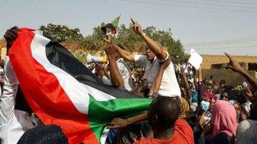 Des manifestants brandissent le drapeau soudanais lors d'un rassemblement contre le régime du président Omar el-Béchir à Omdourman, ville jumelle de Khartoum, le 31 janvier 2019