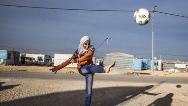 """Tous les matins, dans le camp de réfugiés syriens de Zaatari, des dizaines de fillettes foulent le terrain à l'abri des regards et de la pression de la communauté. Avec ceci de supplémentaire qu'ici, le football casse le rythme du camp et éloigne autant que faire se peut de la réalité de la vie en exil. « Quand on monte sur le terrain, c'est une autre vie qui commence"""", explique Sahar, originaire de Deraa. Les entraînements de foot sont une opportunité de « vivre une vie normale », analyse Amal Al Hichan. C'est elle qui les a initié et qui les coordonne alors que depuis 2013 déjà, l'UEFA et la coopération allemande forment les coaches qui encadrent les filles. Dans une société chamboulée par les arrivées de réfugiés, le football fait office de liant. « Il participe à cette essentielle mixité sociale, parfois problématique dans le pays », analyse Soleen Al Zoubi."""