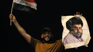 Un Irakien brandit le portrait du chef nationaliste chiite Moqtada Sadr, un des vainqueurs des législatives du week end en Irak, le 14 mai 2018 à Bagdad