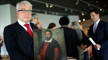 """Markus H. Stoetzel, avocat représentant August Liebmann Mayer, pose avec la toile restituée, """"Portrait d'un homme"""""""
