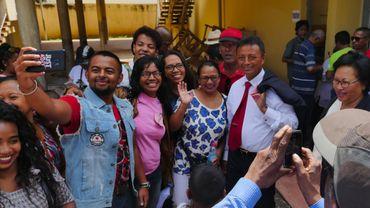Le candidat Marc Ravalomanana (à droite, cravate rouge) pose pour un selfie avec ses partisans à la sortie du bureau de vote.
