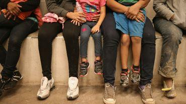 Des femmes et des enfants assis dans une cellule de détention à la frontière américano-mexicaine le 8 septembre 2014