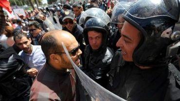 """Un manifestant face à des policiers lors de la La commémoration de la """"journée des martyrs"""" à Tunis, le 9 avril 2012"""