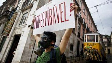 """Un homme tient un poster avec l'inscription """"irrespirable"""" le 28 may 2011, lors d'une manifestation contre l'austérité à Lisbonne, au Portugal"""