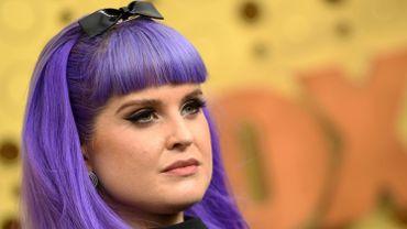 Kelly Osbourne a ajouté un noeud pour accessoiriser sa coiffure violette. Elle a mis l'accent sur son regard avec de longs cils effet plume pour adoucir son look voyant.