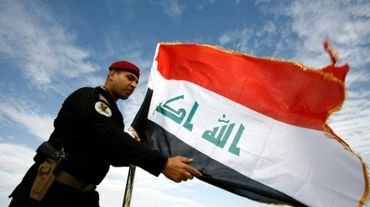 Un policier irakien devant le drapeau de l'Irak, à Najaf le 9 janvier 2016