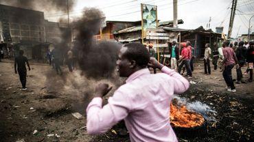 Des habitants marchent près de barricades en flammes dans le bidonville de Mathare à Nairobi, le 9 août 2017. Ils protestent contre les résultats de l'élection présidentielle au Kenya.