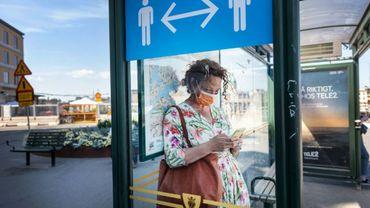 Une passante à Stockholm, le 26 juin 2020 devant une affiche recommandant la distanciation sociale