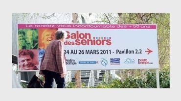 Une personne passe le 24 mars 2011 devant le panneau annonçant le Salon des seniors qui se tient Porte de Versailles à Paris