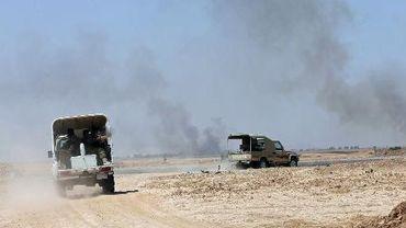 Un véhicule de soldats Peshmerga passe devant un nuage de fumée venant d'une zone contrôlée par les jihadistes à 20 kilomètres de Kirkouk en Irak, le 29 juin 2014