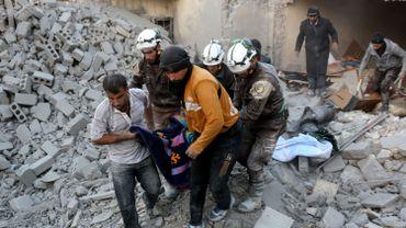 """Des hommes de la défense civile, plus connus sous les noms de """"Casques blancs"""", sortent une victime des décombres après un bombardement sur Alep."""