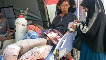 Blessé dans le séisme meurtrier en Indonésie, Alimuddin (G) allongé sur un lit de fortune patiente avec son épouse Maria Ulfa (D) devant un hôpital de Mataram sur l'île de Lombok, le 6 août 2018