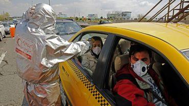 Un membre de la Croix-Rouge iranienne prend la température des passagers d'un taxi, le 26 mars 2020, près de Téhéran, pendant l'épidémie de coronavirus en Iran