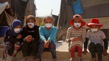 Des jeunes filles syriennes déplacées portent des masques décorés par des artistes lors d'une campagne de sensibilisation au COVID-19 au camp de Bardaqli dans la ville de Dana, dans la province d'Idlib, dans le nord-ouest de la Syrie, le 20 avril 2020