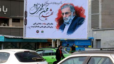 Des véhicules passent devant un panneau d'affichage en l'honneur du scientifique nucléaire Mohsen Fakhrizadeh, tué dans la capitale iranienne, Téhéran, le 30 novembre 2020.