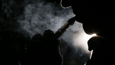 Une personne fume une cigarette électronique