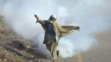 Un manifestant du groupe islamiste TLYRAP renvoie une grenade lacrymogène vers la police pendant un affrontement à Islamabad, le 25 novembre 2017