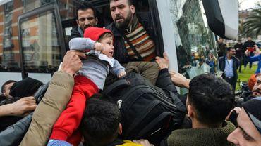 Un enfant est soulevé au-dessus de la tête des migrants qui tentent de monter dans un bus à destination de la frontière grecque, le 28 février 2020 à Istanbul, en Turquie