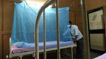 Mise en place d'une moustiquaire au-dessus d'un lit dans un hôpital à Ahmedabad au Pakistan, le 2 novembre 2018