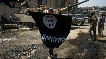 Un membre des troupes d'élite irakiennes brandit un drapeau retourné de l'Etat islamique, le 1er juillet 2017 à Mossoul, en Irak