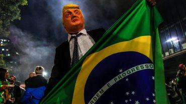 Un partisan du futur président du Brésil Jair Bolsonaro porte un masque à l'éffigie du président américain Donald Trump, le 28 octobre 2018 à Sao Paulo.
