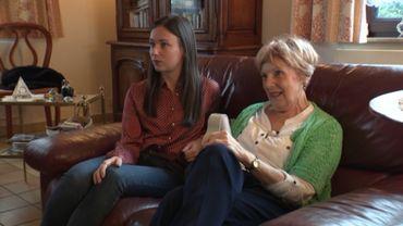 De son salon, Elise regarde sur sa télévision les photos et les vidéos envoyées par sa famille.