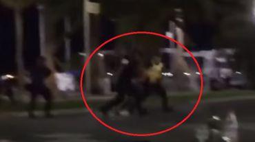 L'homme qui avait été immobilisé à terre par les policiers est emmené de force.