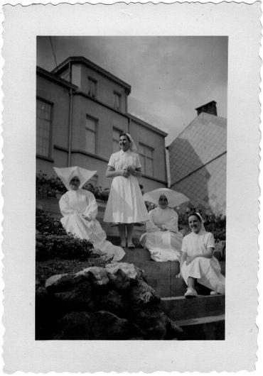 Lucy Deblon Marquet (en bas droite), devant la maison du directeur de l'école d'infirmières, avec deux religieuses et une autre étudiante.