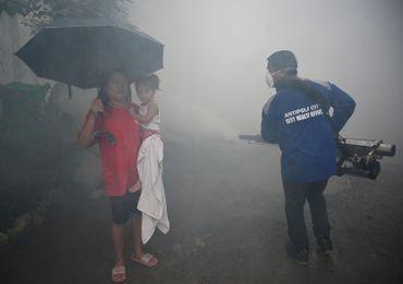 Une petite fille et sa grand-mère assistent à une opération de destruction de larves de moustiques pour réduire la propagation de la dengue dans un village à l'est de Manille.