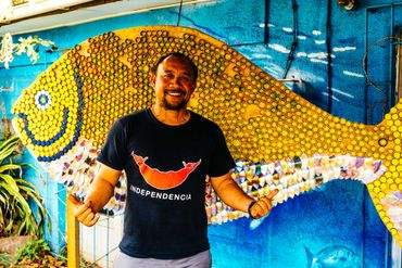 Ludovic Burns Tuki devant le logo de son ONG La Mesa del Mar