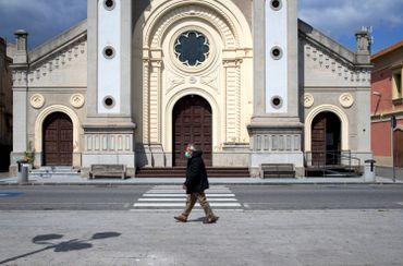 Passant avec un masque devant une église de Locri, en Calabre, le 08 avril 2020
