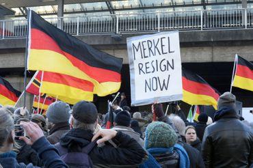 """Des partisans d'extrême droite allemands manifestent à la gare de Cologne le 9 janvier 2016. En scandant """"Merkel out"""" et en agitant des drapeaux allemands, les partisans du mouvement xénophobe PEGIDA exprimaient leur colère contre les migrants."""