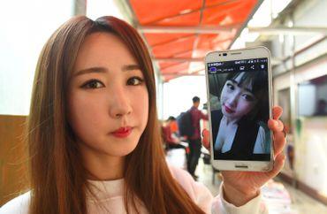 Lee So-Young (Seul-Bee), membre de SixBomb, montre une photo d'elle avant ses opérations de chirurgie esthétique le 16 mars 2017 à Séoul