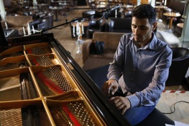 Aeham Ahmad, pianiste syrien et réfugié du camp de réfugiés de Yarmouk à Damas, répète avant un concert le 30 août 2020 dans le centre culturel `` One World '' à Reinstorf près de Lunebourg, dans le nord de l'Allemagne