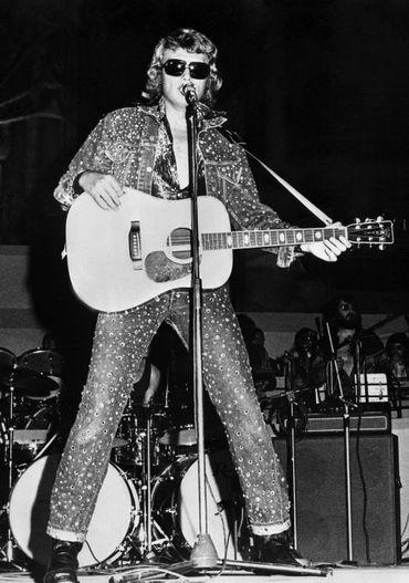 Le denim fait partie intégrante du look de Johnny Hallyday, comme l'atteste cette tenue de scène recouverte de détails glitter. Athènes, juillet 1973