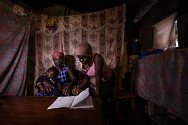 Bella Achieng sort son livre pour montrer les progrès de ses études à sa mère Lilian Adhiambo chez eux à Nairobi, le 7 août 2020.