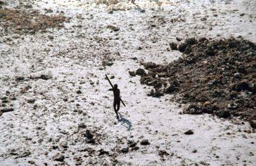 un homme de la tribu Sentinelle pointe son arc et ses flèches sur un hélicoptère des garde-côtes indiens alors qu'il survole l'île Sentinelle Nord, dans les îles Andaman, au lendemain du tsunami de 2004 dans l'océan Indien.
