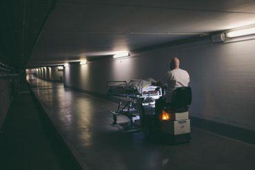 Emmené par un brancardier de l'unité Covid-19 où il est décédé, un patient effectue son dernier voyage jusqu'à la morgue.