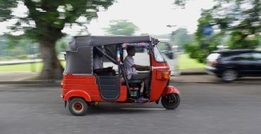 Un homme srilankais conduit un taxi à trois roues, appelé tuk-tuk, dans la ville de Colombo