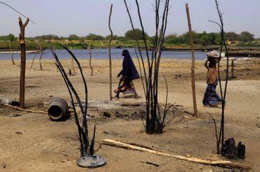 Des femmes tchadiennes marchent près de maisons détruites, dans le village de N'Gouboua, près du Lac Tchad, le 5 mars 2015. Les combattants de Boko Haram militants sont arrivés dans le village le 13 février dernier, ont brûlé des maisons, et tué une dizaine de personnes. Plus de 3 400 Nigérians vivaient dans ce village mais ils ont tous fui.