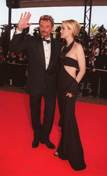 Rockeur dans l'âme, le chanteur français n'hésite pas à troquer ses costumes bariolés pour des smokings et noeuds pap', comme ici au festival de Cannes avec Laeticia. Cannes, mai 1999